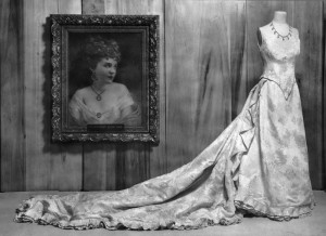 Black and white image of Elizabeth McCort Tabor's wedding dress on display at the Colorado State Historical Society. The dress is displayed on an old-fashioned manikin beside a portrait of Elizabeth McCort Tabor.