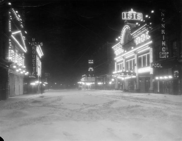 Night view of a snow-covered Curtis Street in Denver, Colorado, circa 1913-1919