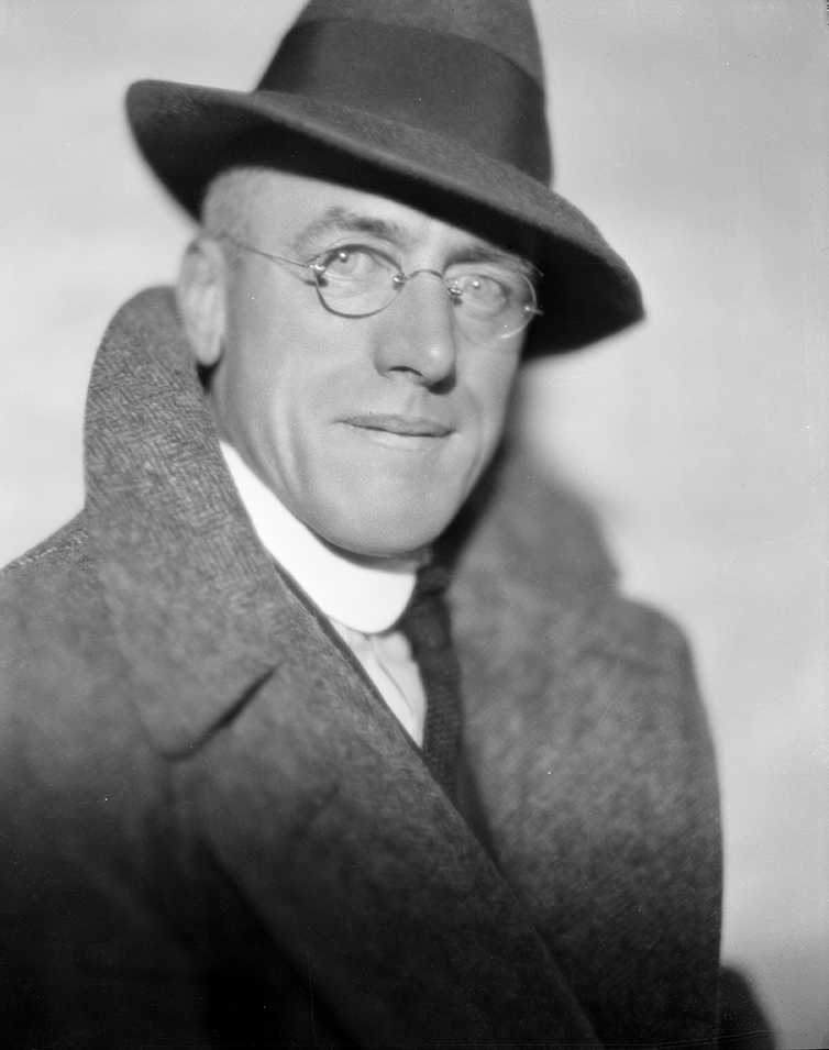 Fred Payne Clatworthy looking debonair, staring into the camera, wearing glasses, a hat, and a peacoat with popped collar.