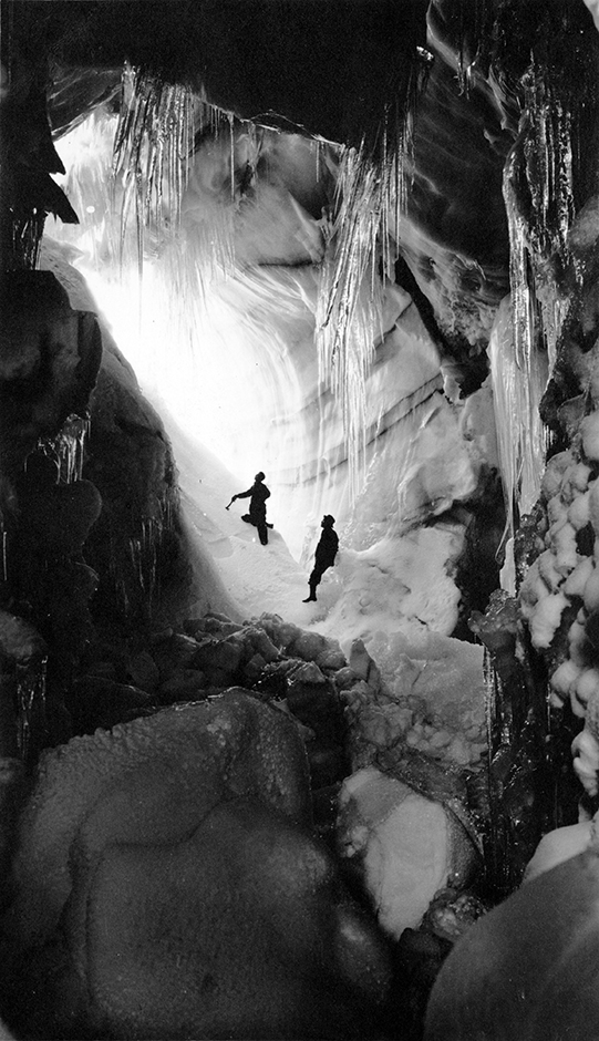 Two people pose in cave at Hawlett (Rowe) Glacier in Rocky Mountain National Park