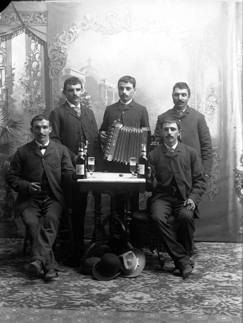 Full-length studio portrait of a group of men, including Peter and Barter, gathered around a table with bottles and glasses of beer. One man holds an accordion.