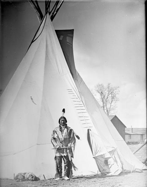 Ute Chief Buckskin Charlie poses in front of a tipi, probably in Ignacio, CO