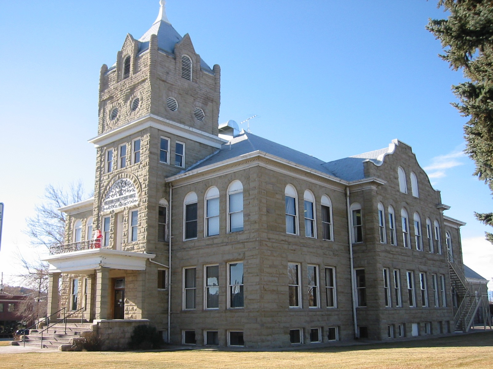 A photo of the historic Huerfano County Courthouse and Jail, a stone, multi-level building with a prominent tower.