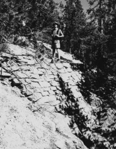Historic black-and-white image showing a hiker standing on East Longs Peak Trail, in the Estes Park vicinity, Boulder/Larimer Counties. The trail was listed in the National Register in 2007.