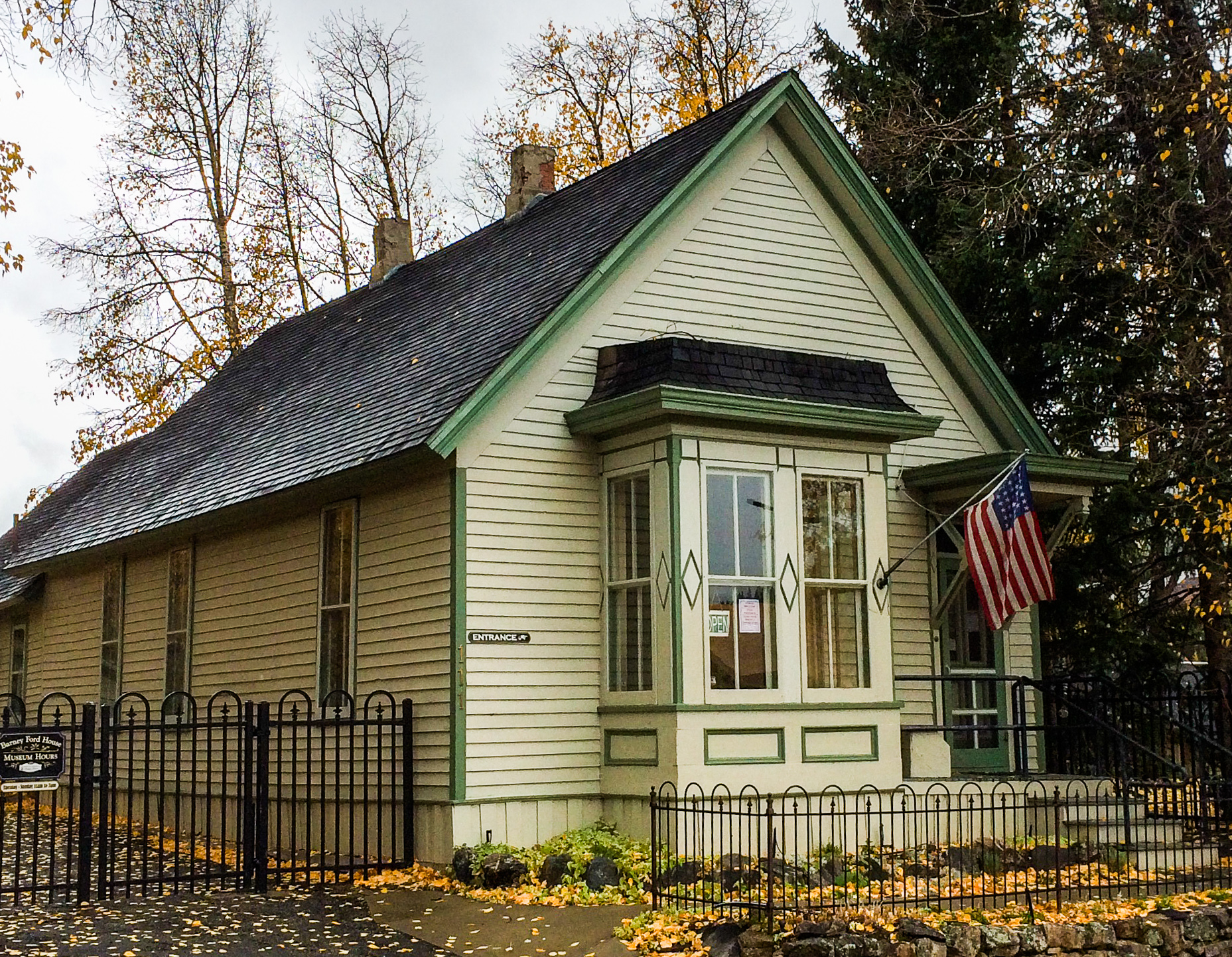 Barney Ford House Museum, light yellow with green trim and an American flag hanging by the front door.
