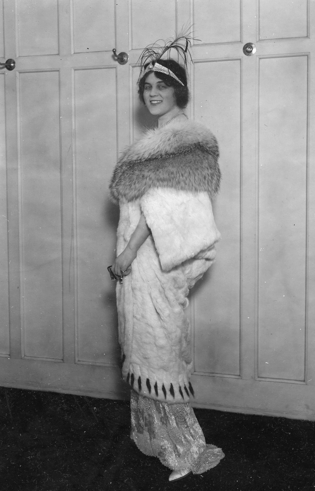 Model Margaret Gessing modeling an opera coat of ermine with white badger collar.