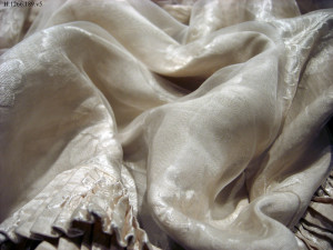 Closeup image of a small portion of Baby Doe Tabor's wedding dress. The fabric is supported by a crepe line encasement which was applied by a textile conservator in 1981.