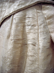 Closeup image of a portion of Baby Doe Tabor's wedding dress, exhibiting deterioration.