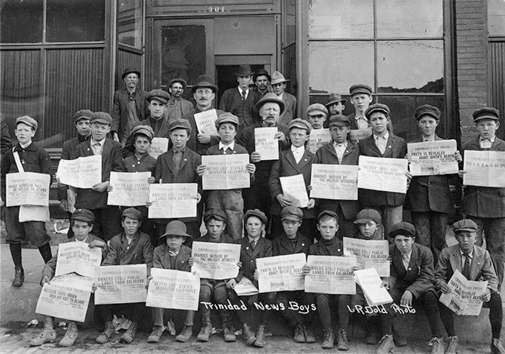 A large group of young boys hold up newspapers showing headlines from the 1914 Ludlow tragedy.