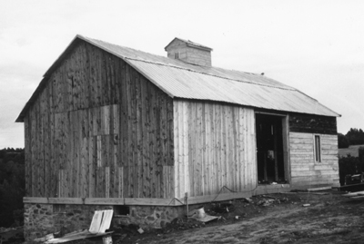 Black-and-white image of a bank barn.