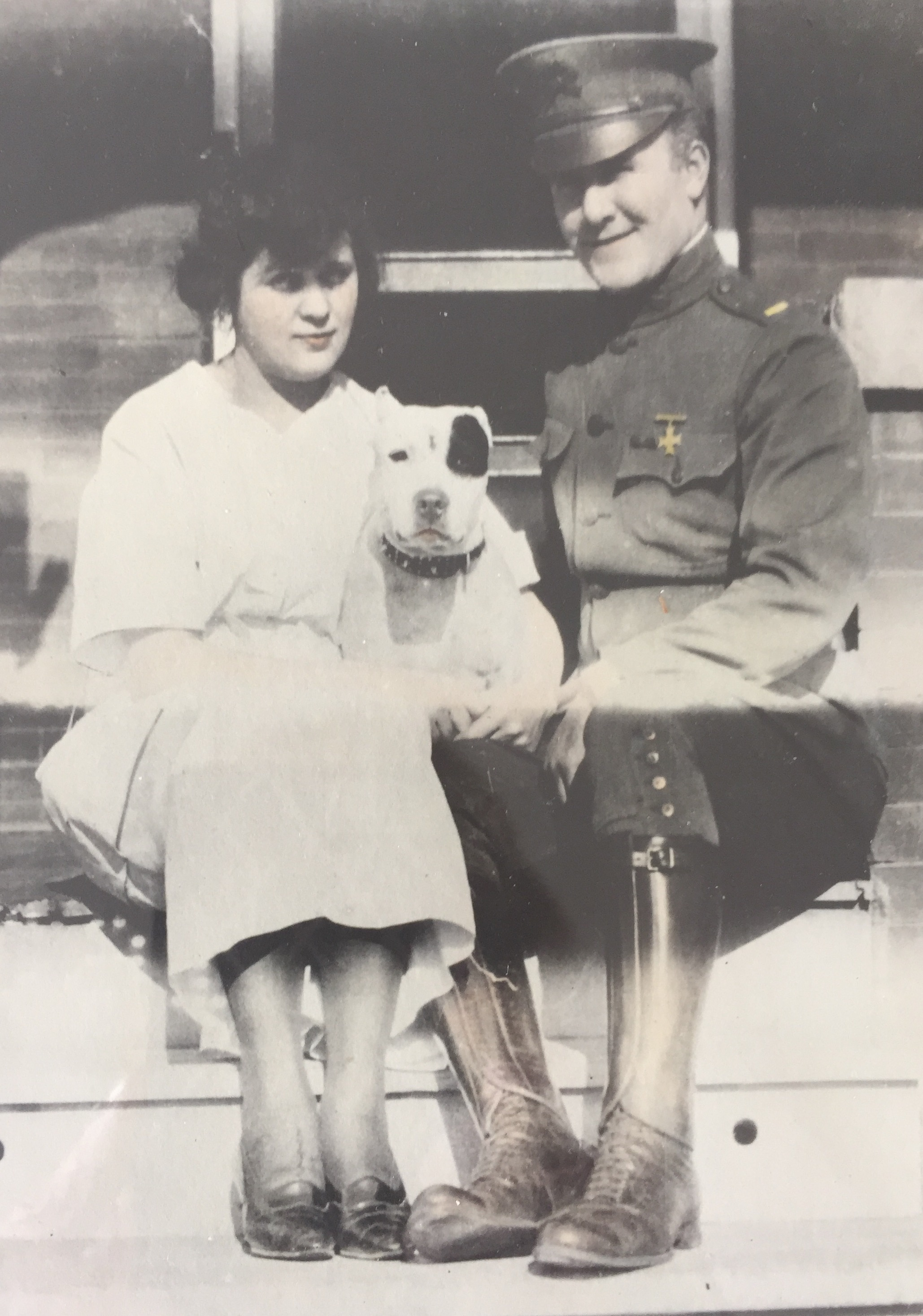 Margaret Gessing and Joe Bona in his World War One uniform sit with a dog between them.