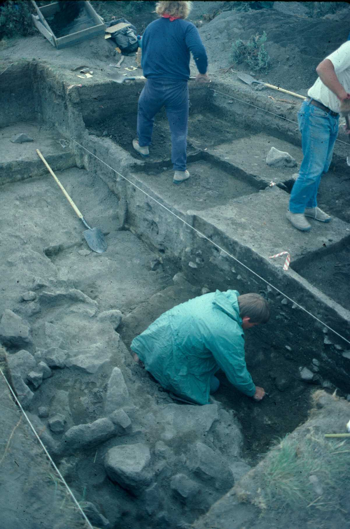 Archaeologists excavating a block of units at a site.