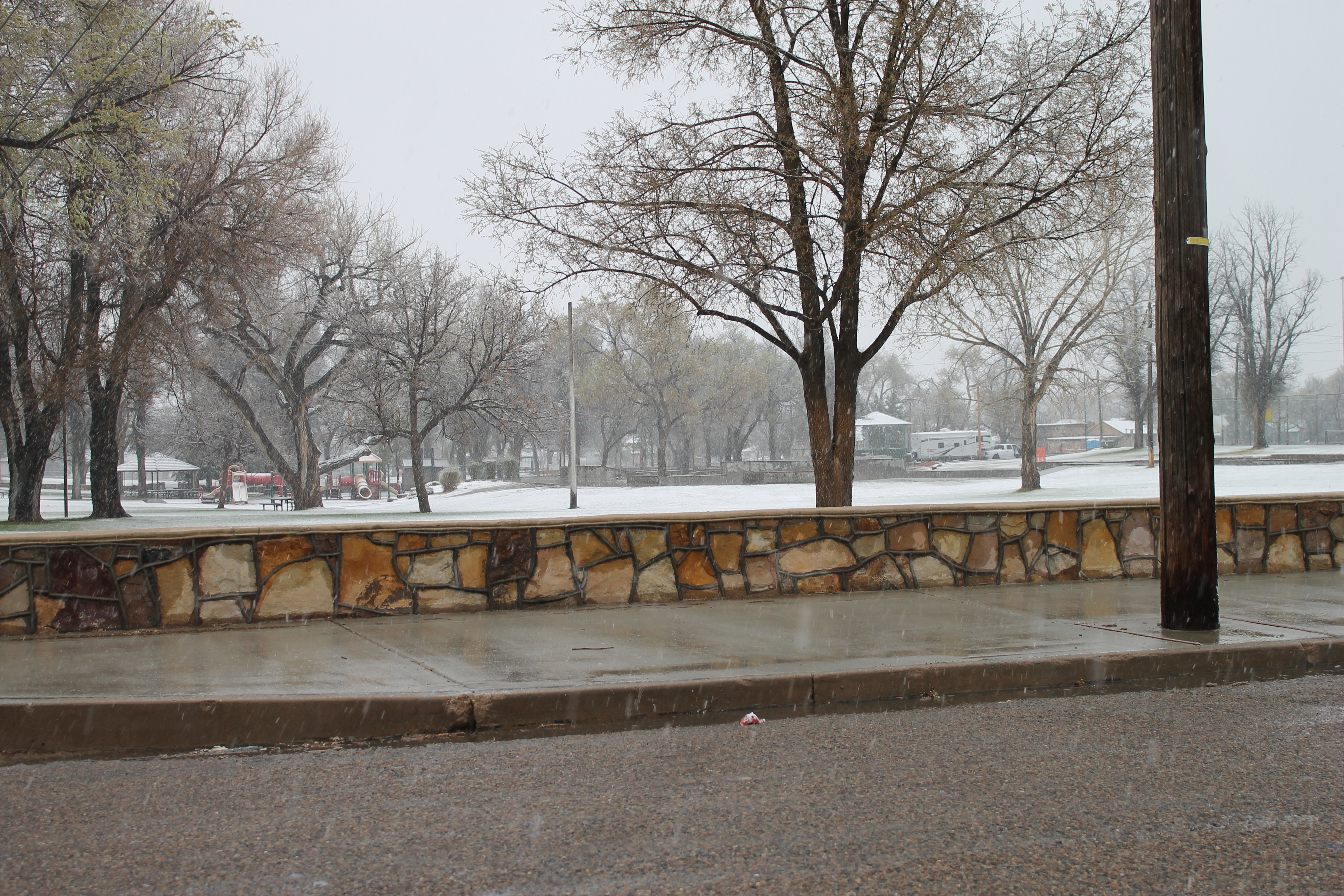 A photo of La Junta City Park Wall, a stone wall a couple of feet high set back from the road. Snow is on the ground.