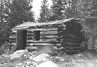 Round log, saddle-notched, side-gabled cabin in Boulder County.
