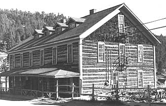 A pioneer log style building with hewn log, side gable with shingle gables.