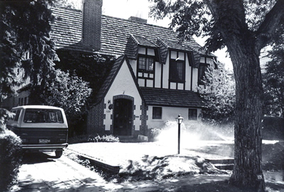 Black and white photo of a Tudor Revival style home.