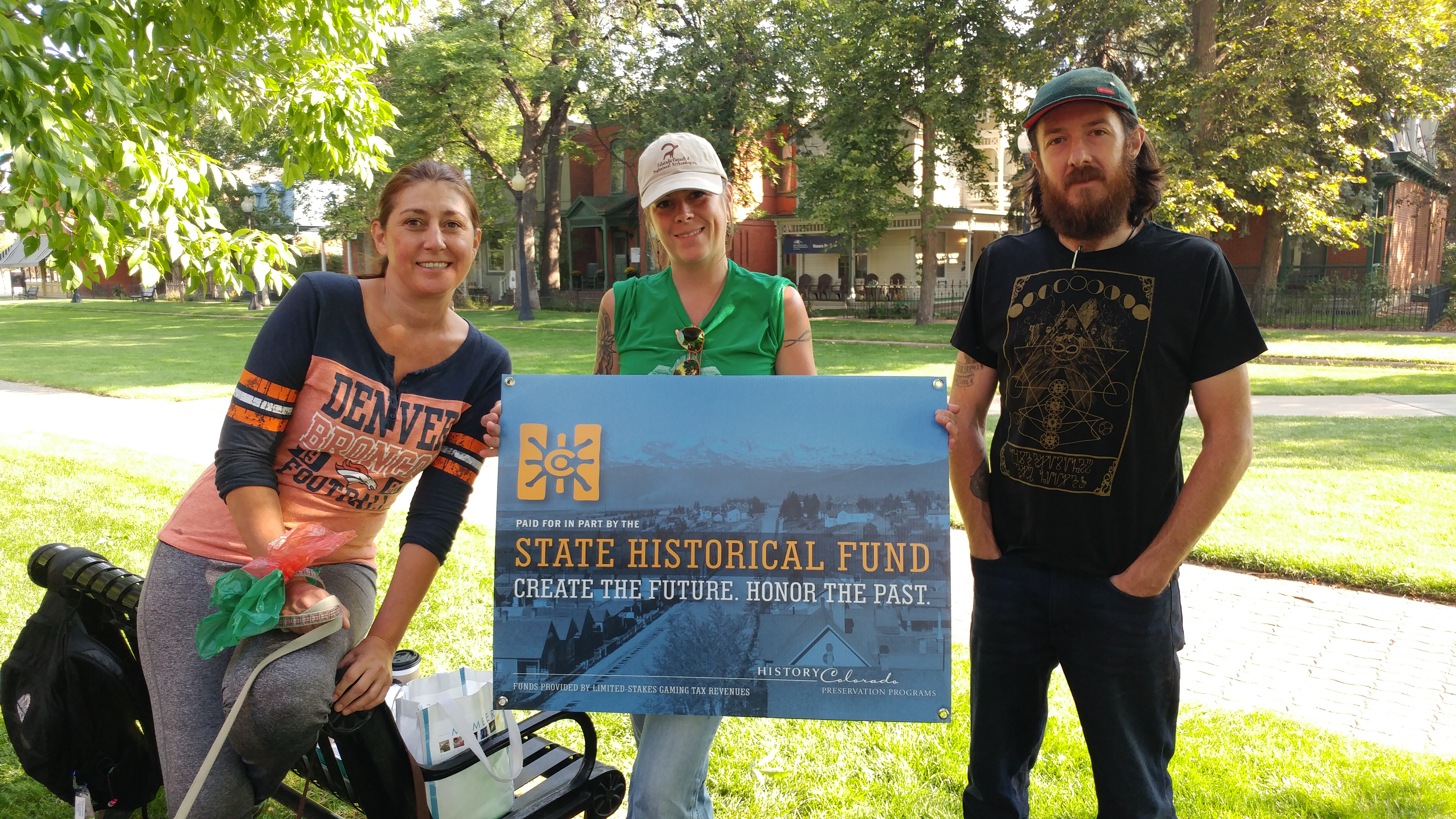 Three students standing in the 9th Street Historic District with a History Colorado State Historical Fund sign.