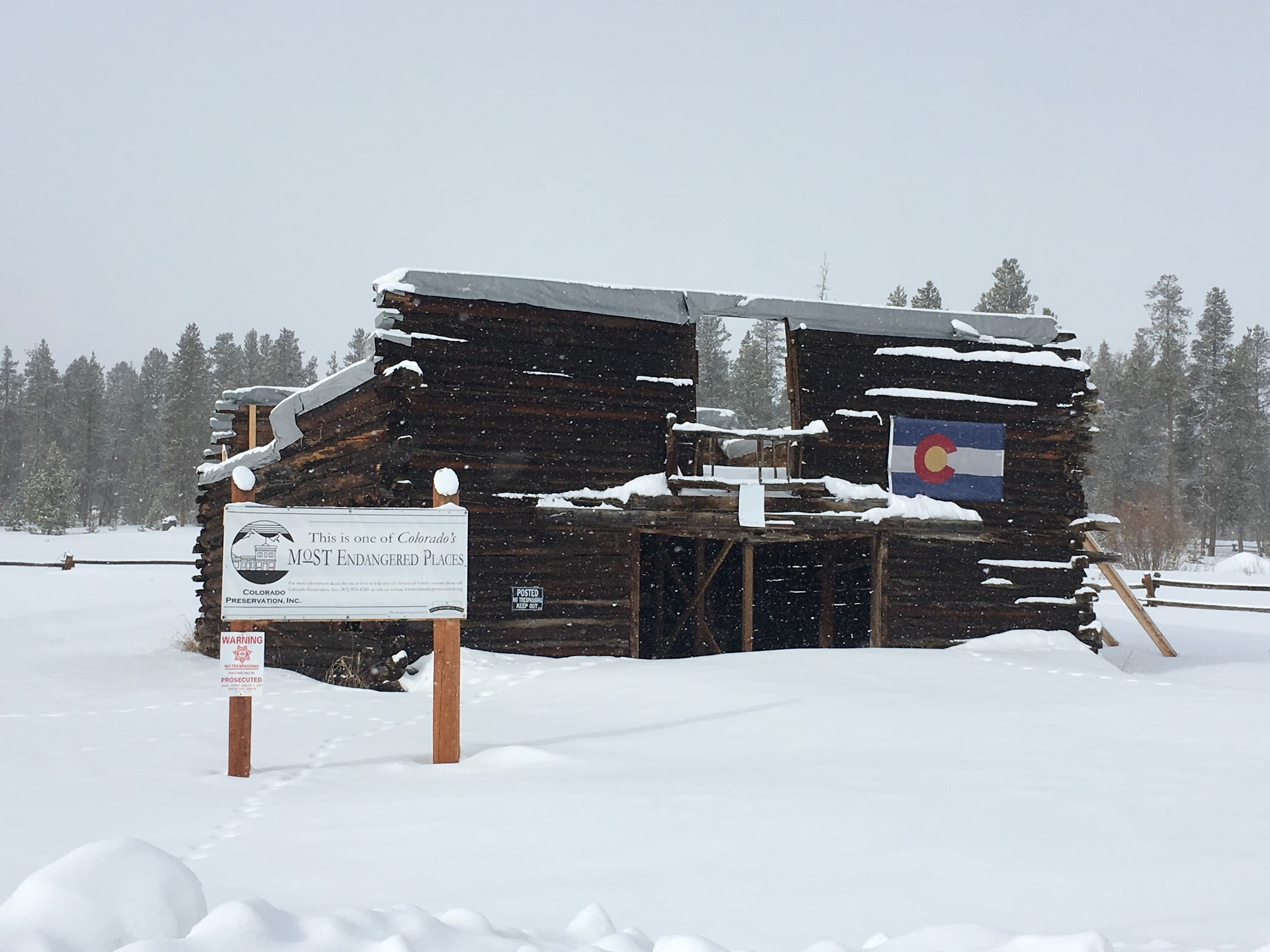 "Th roofless 4 Bar 4 Ranch (Ford Barn) log building in heavy snow with an ""Endangered Places"" sign in front of it."