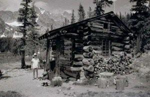 A black and white photo of the cabin with protruding logs on the corners, gabled roof and surrounded by trees. Someone is standing on the left of the cabin and there are prominent mountains in the background on the left.