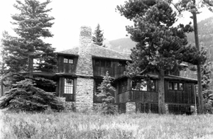 A black and white photo of the ranch house between two large pine trees (1980).