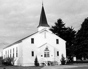 A black and white photo of the chapel from a slight angle with evergreen trees on the right side.