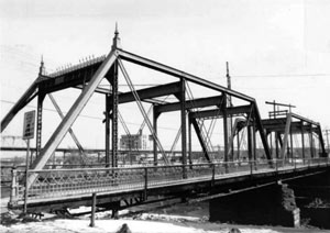 A black and white photo of the bridge with double truss and railing on the platform.