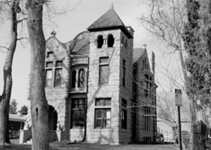 A black and white photo of the tall house with large leafless trees in the foreground and square corner tower in the center.