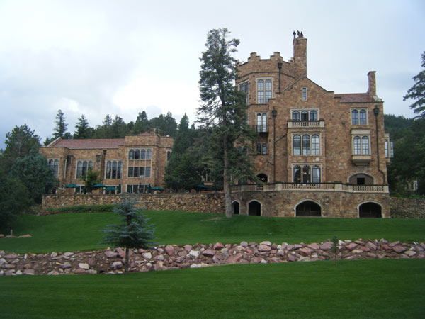 A photo of the castle and carriage house on the grounds with vibrant green grass and pine trees throughout the picture.