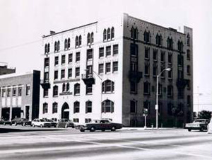A black and white photo of the building in front of the street.