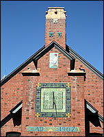 A photo of the top of the building with a sun dial and chimney.