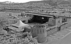 An overhead photo of the fort in black and white with adobe with towers and hills in the background.