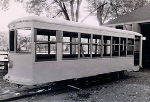 A black and white photo of the broadside of the streetcar with windows open sitting on the tracks below.