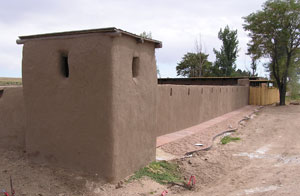A picture of the fort from an angle with adobe walls and towers on the corner with red dirt and tree on the right corner.