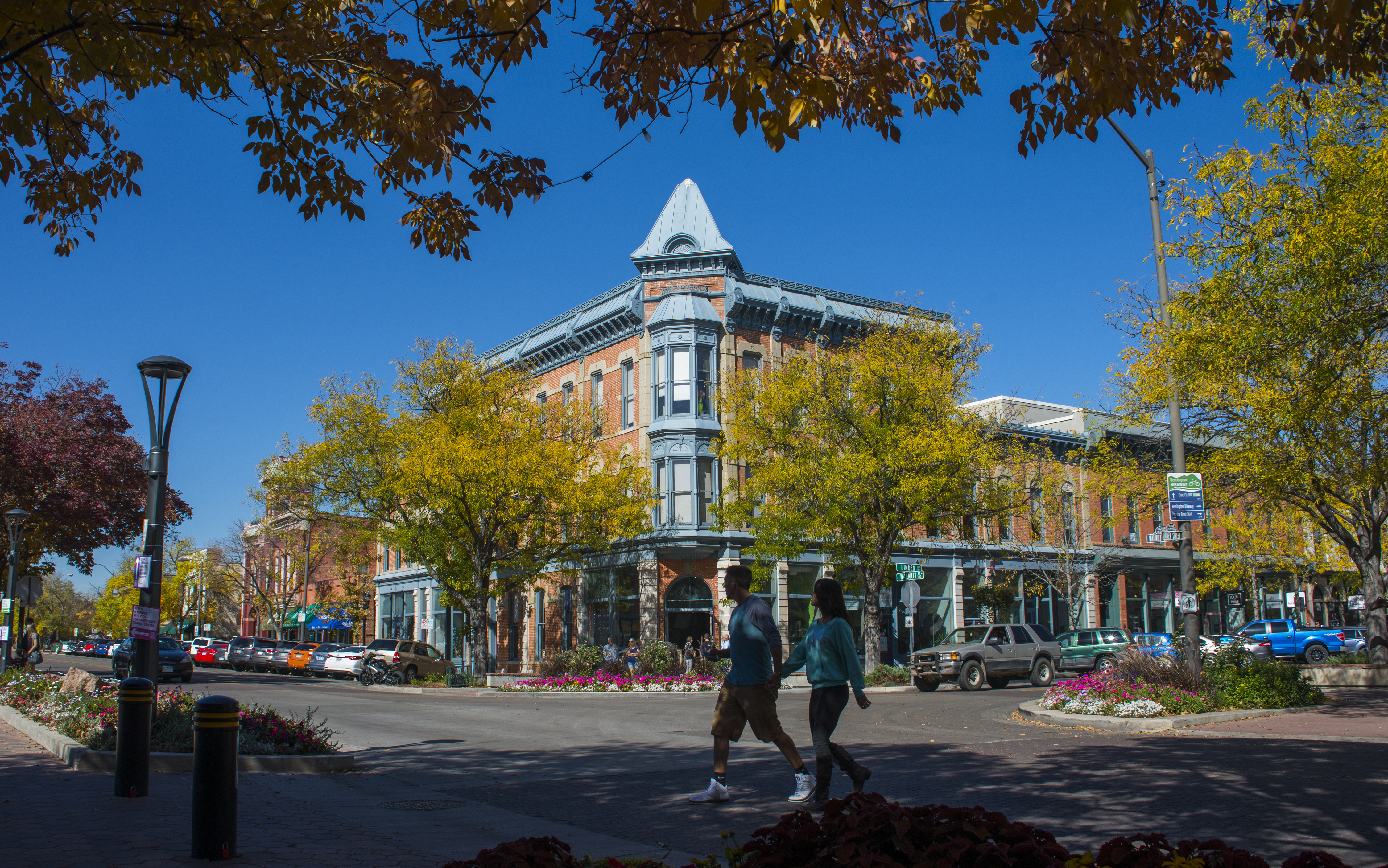 Fort Collins' historic Old Town district in the fall, with people walking along the street.