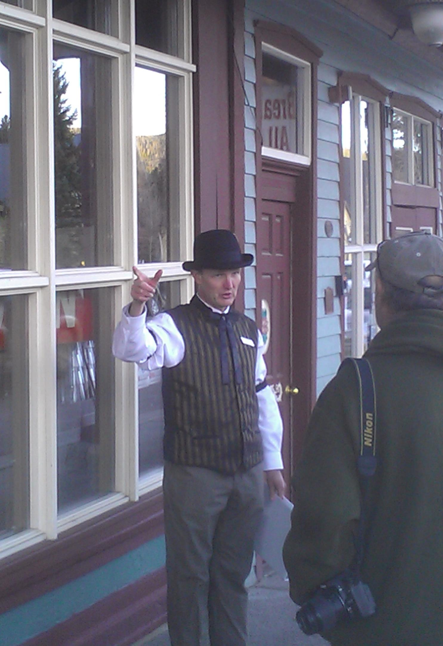 A tour guide dressed in historic costume discusses the history of Breckenridge's saloons.