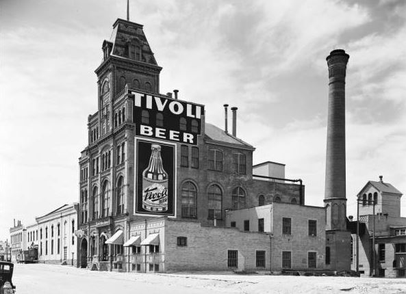 "View of the Tivoli-Union Brewery and offices at 10th (Tenth) and Larimer Streets in the Auraria neighborhood of Denver, Colorado. The four-story brick building has arched windows, decorative brick work, canvas awnings and a tower with a mansard roof. A sign reads: ""Tivoli Beer."" Shows smokestacks, chimneys, an automobile, truck and fire hydrant."
