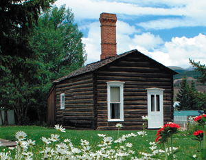 A picture of the cabin with gabled roof, dark brown log walls and white windows and door with brick chimney on top before a yard of green grass and colorful flowers next to large trees on the left.