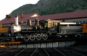 A picture of the locomotive in the center of a roundhouse track with gabled roof behind it and mountains rising in the background.
