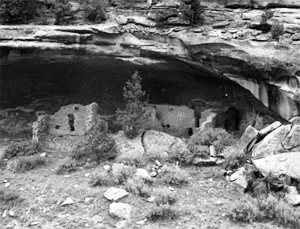 A black and white photo of some ruins beneath a rock structure.