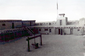 A black and white photo of the fort from the interior with walls on the side, tower on the right and well in the center.