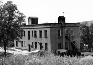 A black and white photo of the hospital with two stories, two sheds on the flat roof on top and a tree on the left.