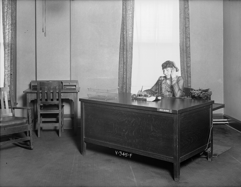 A woman, possibly Blanche M. McFann, sits at a desk in an office at the Mountain States Telephone and Telegraph building at 1421 Champa Street in Denver, Colorado.