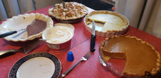Photo of a dining table covered in a red table cloth, several homemade pies on display. A pumpkin pie has a large piece cut from it, while a pie with a custard topping is missing one quarter. A lattice-topped pie toward the back of the table has yet to be cut, while the chocolate pie in front of it is nearly gone. Various pieces of cutlery, as well as a tub of whipped topping and a dessert plate, are also on the table.
