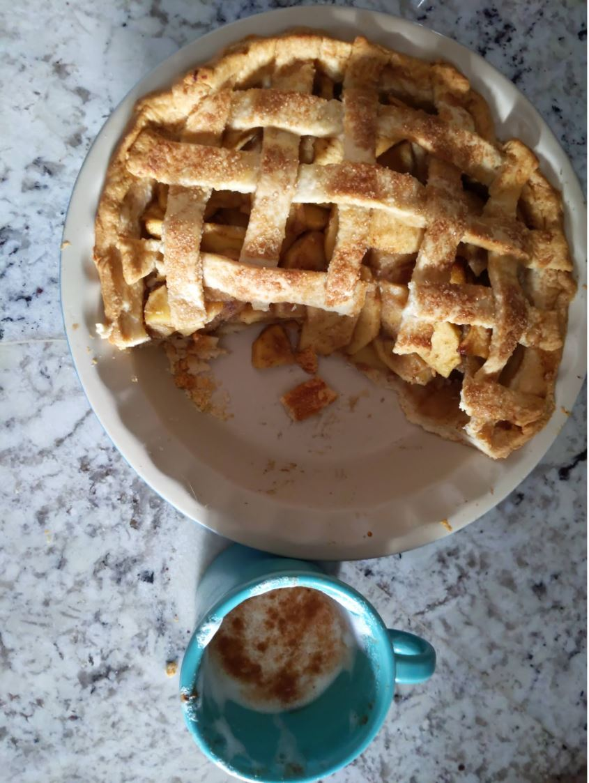 Photo looking directly down at a homemade apple pie, sitting atop a gray and white granite countertop. The pie has been baked in a white stoneware pie plate, and about one-third of the pie is already gone. The pie is apple, with a golden lattice top that is sprinkled with sugar. Next to the pie plate, there is a turquoise coffee cup that had latte in it, although nearly all of the coffee has been enjoyed and just the foam, sprinkled with cinnamon, remains.