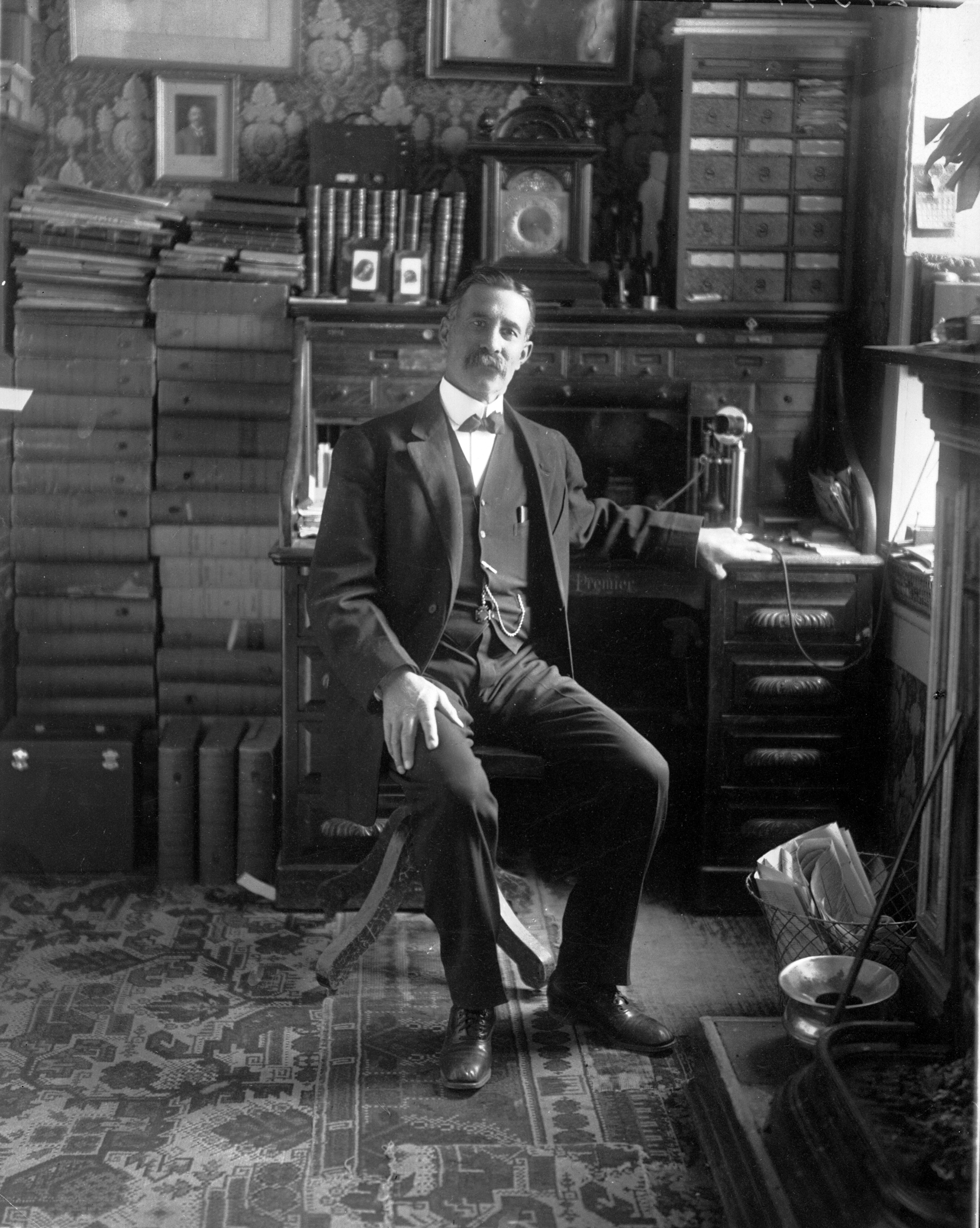 Photo of Casimiro Barela, seated in his office. He is dressed in a suit with a waistcoat and pocketwatch, and a bowtie. His desk, on which stands a telephone, is surrounded by books which stand along the top of his desk as well as in tall stacks adjacent to the desk. An elaborate carriage clock sits atop his desk and there are several framed photos which are sitting on his desk and are hanging on the wall behind him.