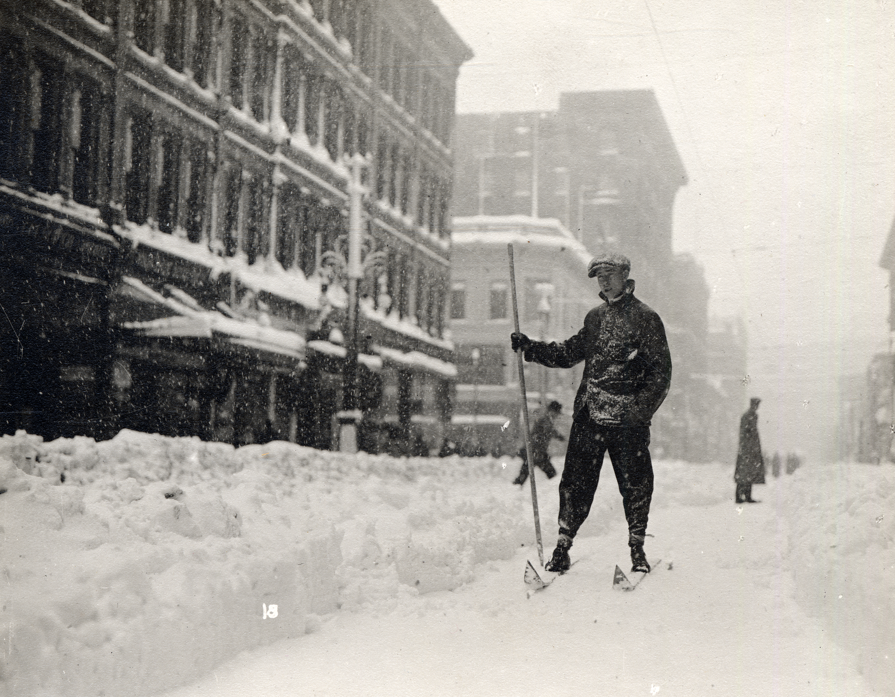 Photo of a young man on skis and holding a pole while skiing through the snow-covered street of downtown Denver. Snow is falling, and there is a narrow path cleared between large snowdrifts on what would be the city street.