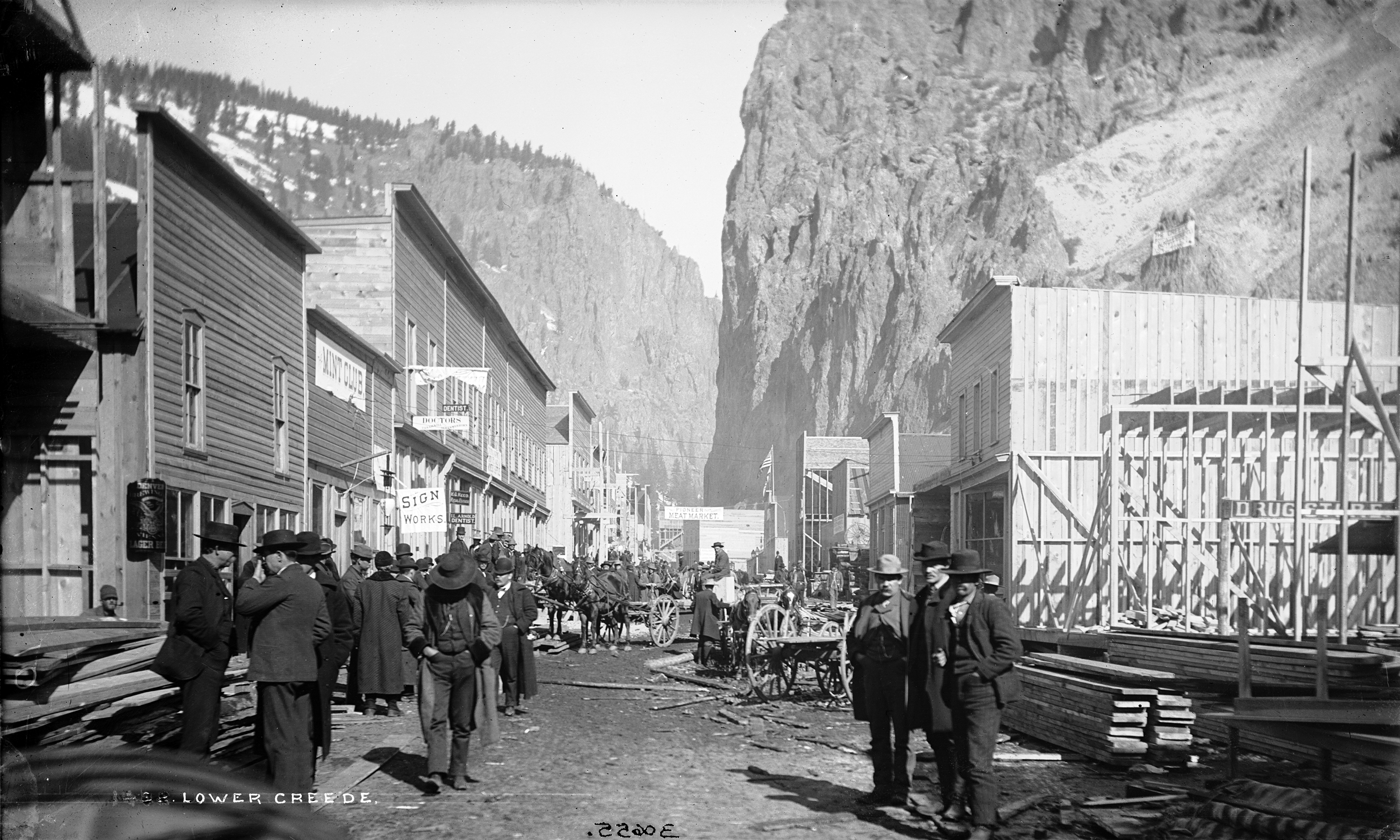 Photo of a street in downtown Creede, Colorado, in the 1890s. Several wooden buildings line each side of the dirt street, while other buildings are under construction and pallets of building materials sit on the sides of the street. Men dressed in suits and hats are seen walking and standing around talking with others as horse-drawn wagons traverse the road.