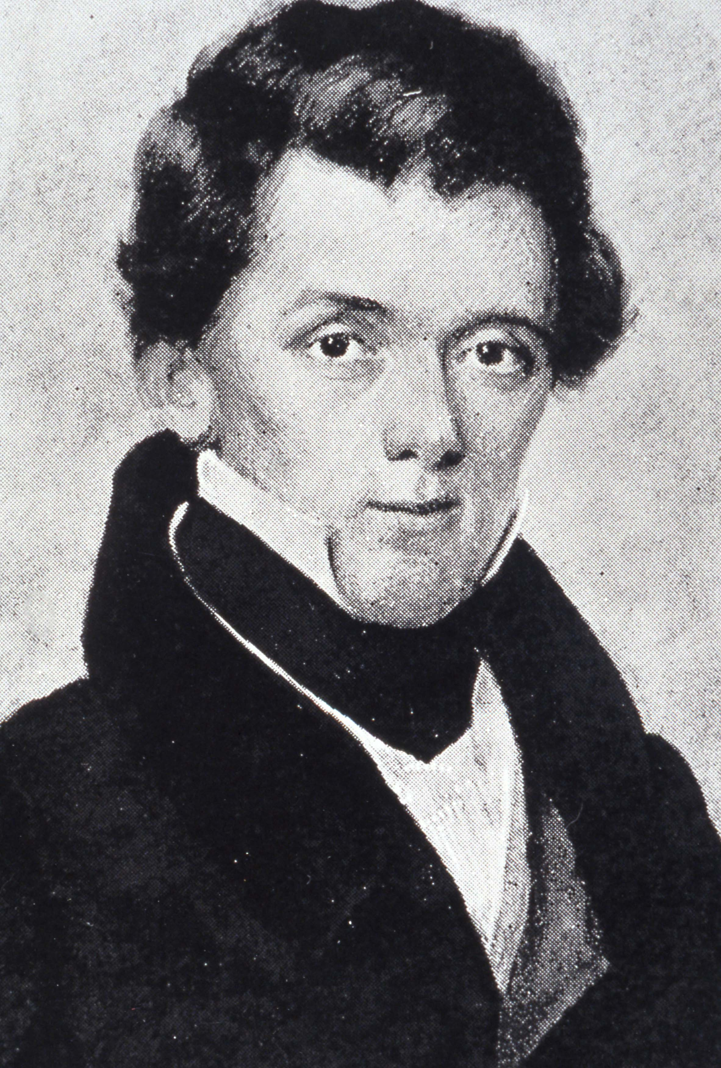 This image is a portrait of naturalist Edwin James. He has dark longer hair which appears to be pulled to the back of his head, and he wears a jacket with the collar up, and underneath is a high-collared white dress shirt.