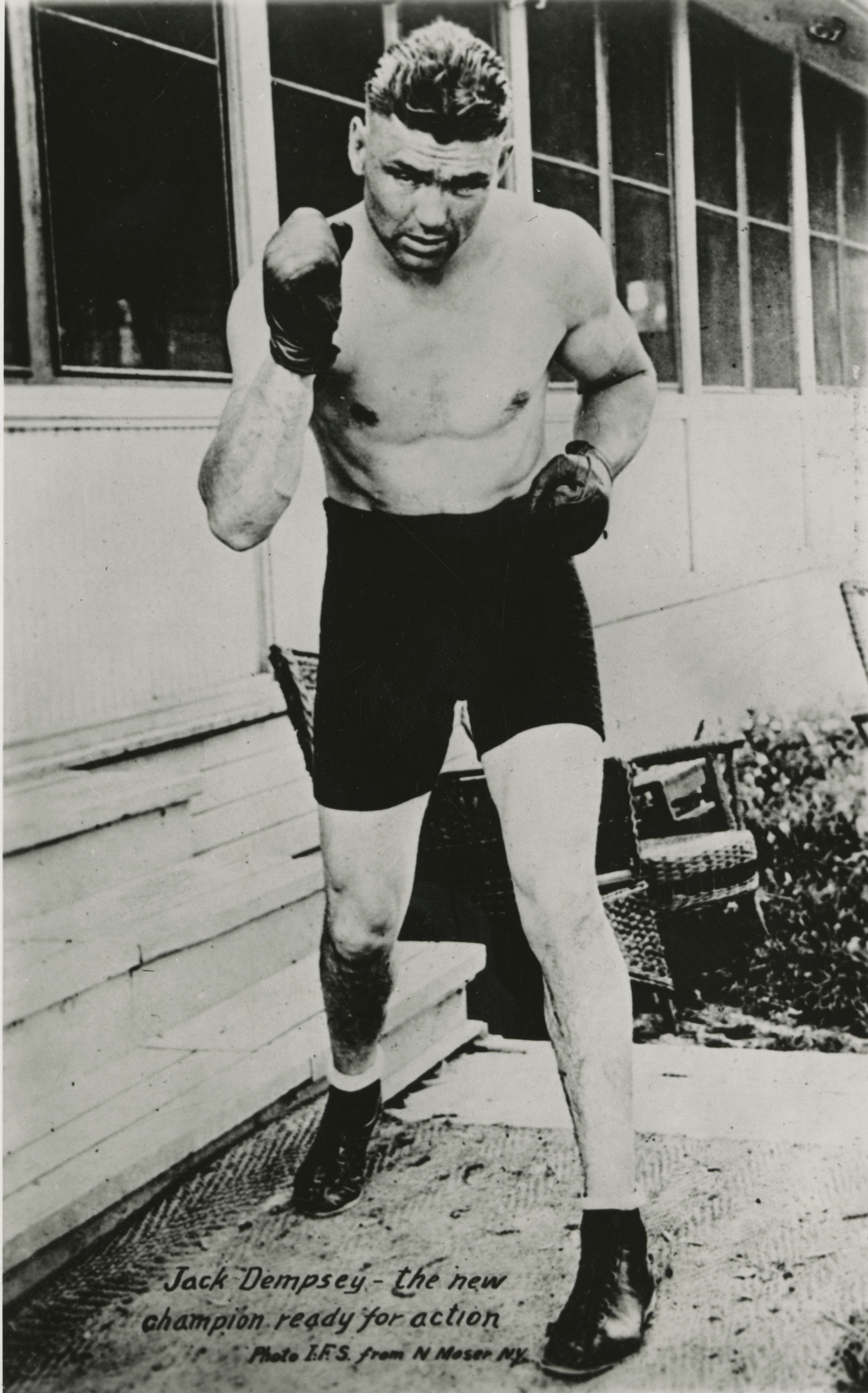 "Photo of boxer Jack Dempsey, known as the ""Manassa Mauler,"" having defended his title of World Heavyweight Champion in 1920. The fighter stands in front of a building, posing as if he will deliver a punch. He is dressed as if he is ready to return to the ring, wearing black boxing shorts, ankle boots, and boxing gloves."