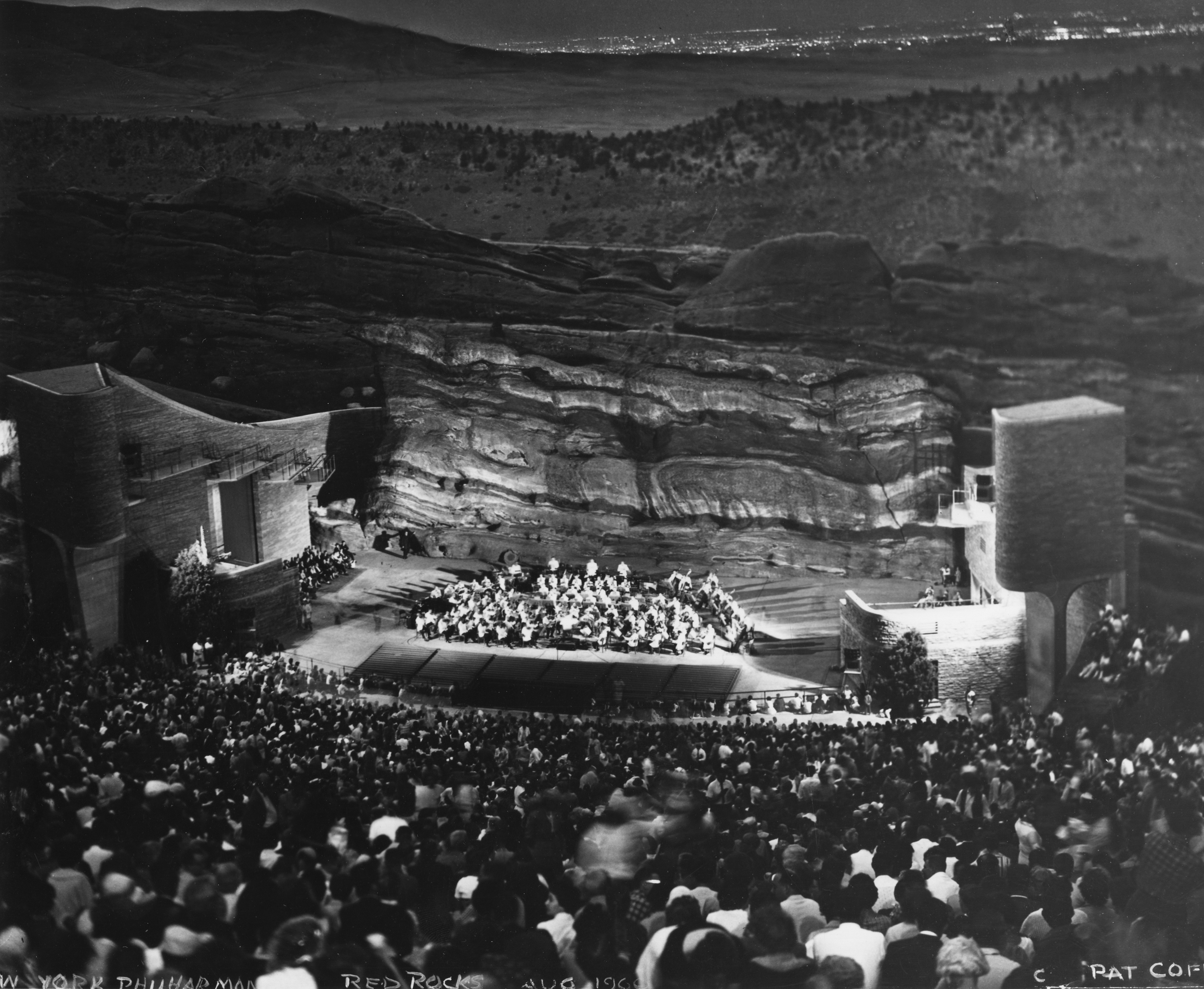 Photo of Red Rocks Amphitheatre hosting its inaugural concert in the summer of 1960. Here, the New York Philharmonic performs on the stage below, to a packed crowd. Behind the stage stand iconic red rock walls, and the city lights of Denver are visible on the horizon.